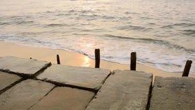 与黏附被毁坏的木篱芭的老具体堤防反对海波浪背景在日落期间的 股票录像