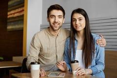 与黑发的美好的年轻对在便衣微笑,饮用的咖啡和摆在照片的在大学文章上 图库摄影