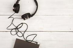 与黑名册和耳机的音频书概念在木背景 库存照片