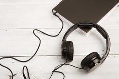 与黑名册和耳机的音频书概念在白色木背景 免版税库存图片