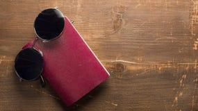 与黑太阳镜的空白的护照在木背景 免版税库存图片
