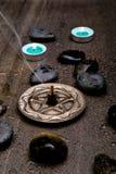 与黑岩石的绿松石蜡烛和与公司的银色五角星形 免版税库存图片