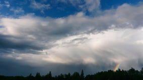 与黑暗和光的剧烈的天空覆盖与彩虹 图库摄影