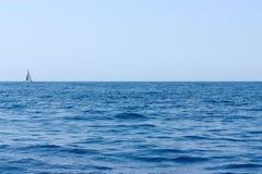 与黑暗波浪和一条偏僻的白色游艇的海水风景在天际在晴天 免版税库存照片