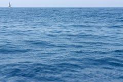 与黑暗波浪和一条偏僻的白色游艇的海水风景在天际在晴天 库存图片