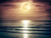 与黑暗的云彩和明亮的满月的五颜六色的天空在海景 库存照片