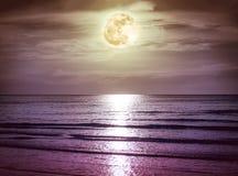 与黑暗的云彩和明亮的满月的五颜六色的天空在海景 免版税库存图片