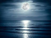 与黑暗的云彩和明亮的满月的五颜六色的天空在海景 免版税图库摄影