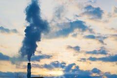 与黑暗的云彩的天空在晚上日落和黑烟从烟囱,摘要, 免版税库存照片