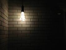 与黑暗的光的老空白陶瓷墙壁纹理从电灯泡 图库摄影