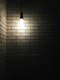 与黑暗的光的老空白陶瓷墙壁纹理从电灯泡 免版税库存照片