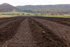 与黑暗的土壤的被耕的农业领域 库存图片