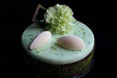 与黑暗的巧克力边界、vanlla奶油甜点和绿色康乃馨花的浅绿色的开心果蛋糕 库存照片