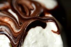 与黑暗的巧克力选矿特写镜头的剧烈的白色冰淇淋 免版税库存照片