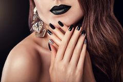 与黑暗的构成、长的头发和黑和银色时髦修指甲佩带的首饰的时装模特儿 黑色唇膏 免版税库存图片