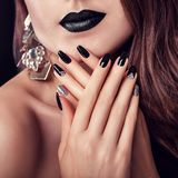 与黑暗的构成、长的头发和黑和银色时髦修指甲佩带的首饰的时装模特儿 黑色唇膏 库存图片