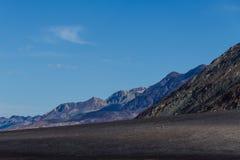 与黑暗的火山的地球的贫瘠沙漠风景和后退入距离的坚固性山脉 库存图片