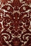 与黑暗的酒颜色刺绣样式的古色古香的织品 免版税库存照片