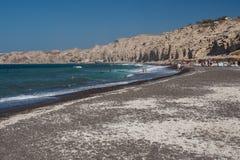 与黑沙子的Vlychada海滩在异常的形状的峭壁下 库存图片
