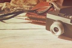 与黑皮革案件和天鹅绒葡萄酒照片的减速火箭的老照相机在白色木背景复制空间 免版税库存图片