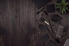 与黑空白的文具,咖啡,植物,电话,作为边界的拷贝空间的现代minimalistic工作区在黑木板 库存照片