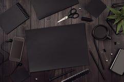与黑空白的文具,咖啡,绿色植物,在黑木板的电话的现代工作区 库存照片