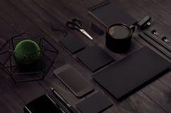 与黑空白的文具,咖啡,绿色植物,在黑木板,顶视图的电话的现代minimalistic工作区,倾斜 库存图片