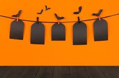 与黑空白的销售标签和黑暗的木板的万圣夜乐趣橙色背景,嘲笑  免版税库存照片