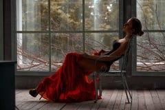 与黑组合和红色礼服的美丽的女性画象 图库摄影