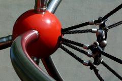 与黑绳索的红色塑料球窝接头在操场 免版税库存照片