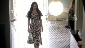 与黑色头发的迷人的年轻西班牙女孩模型在一件长的透明礼服,优美地穿过自助食堂大厅 概念f 股票视频