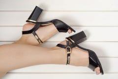 与黑色的女性脚穿上鞋子凉鞋 免版税图库摄影