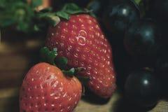 与黑色的红色 草莓和黑葡萄 免版税库存照片