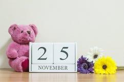 与黑色11月25日词的特写镜头表面白色木日历在棕色木书桌上和奶油在屋子被构造的ba里上色墙纸 免版税库存照片