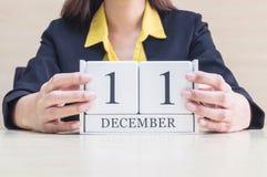 与黑色12月11日词的特写镜头白色木日历在木书桌上的被弄脏的职业妇女手上在办公室屋子,有选择性的fo里 免版税库存照片