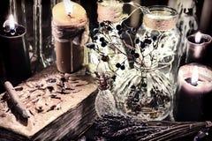 与黑蜡烛,玻璃瓶、毒物莓果和草本的邪恶的书在巫婆桌上 库存照片