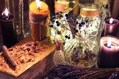 与黑蜡烛,玻璃瓶和草本的邪恶的书在巫婆桌上 免版税库存照片