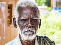 与黑褐色起皱纹的面孔和白发的一张unidentifed老资深印度人贫困者画象和白色胡须,看起来严肃 免版税图库摄影
