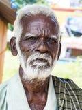 与黑褐色起皱纹的面孔和白发的一张unidentifed老资深印度人贫困者画象和白色胡须,看起来严肃 图库摄影