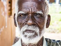 与黑褐色起皱纹的面孔和白发的一张unidentifed老资深印度人贫困者画象和白色胡须,看起来严肃 库存照片