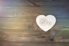 与齿轮的心脏形状在木背景 图库摄影