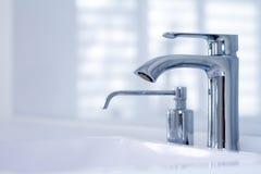 与龙头在minimalistic样式和固定肥皂分配器的一个现代水龙头水槽在昂贵的顶楼卫生间,软的焦点里 图库摄影