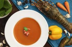 与龙虾的龙虾汤在蓝色土气背景 免版税库存图片