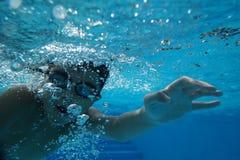 与水下游泳的风镜的愉快的年轻亚洲孩子 免版税库存照片