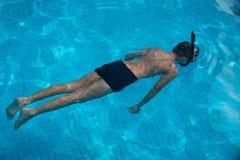 与水下游泳的风镜的愉快的年轻亚洲孩子 免版税库存图片