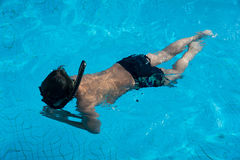 与水下游泳的风镜的愉快的年轻亚洲孩子 图库摄影