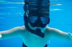 与水下游泳的风镜的愉快的年轻亚洲孩子 库存照片