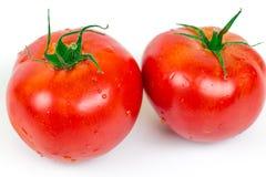 与水下落的两个新鲜的蕃茄 图库摄影