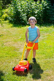 与从事园艺的愉快的小男孩帮助与他的割草机 免版税图库摄影