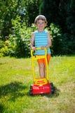 与从事园艺的愉快的小男孩帮助与他的割草机 库存照片